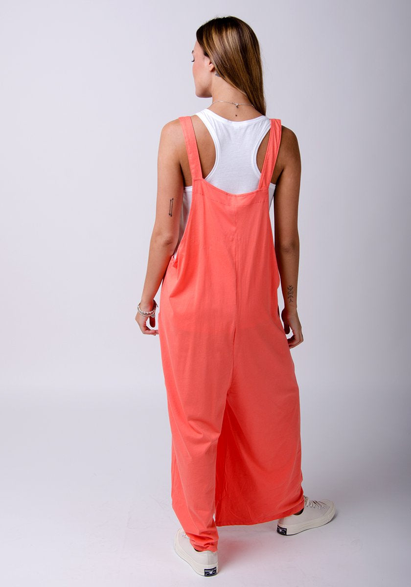 Rear full-length pose with Amber-style, coral, cotton jersey, relaxed-fit dungarees showing adjustable straps.