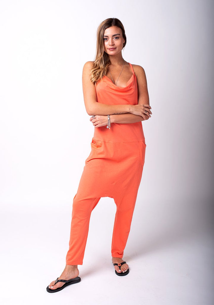 Full frontal pose with weight on left hip and arms crossed, wearing harem trousers style coral jersey jumpsuit.