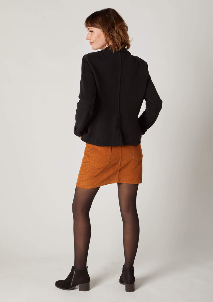 Full back view of autumnal, corduroy mini-skirt, paired with black casual blazer.