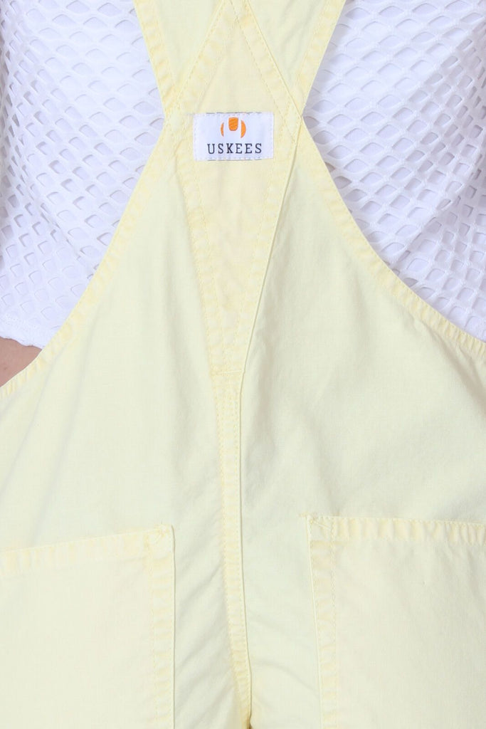 Back of ladies' light yellow, relaxed fit bib overall shorts with clear view of cross straps and branding label.