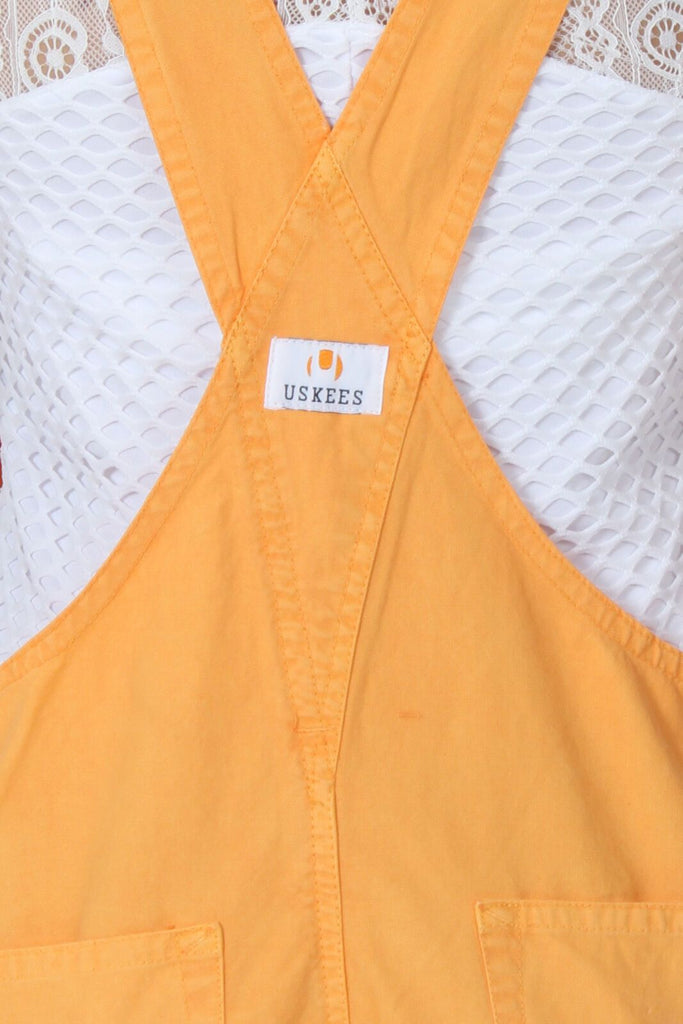 Back of ladies' orange, relaxed fit bib overall shorts with view of cross straps and branding label.