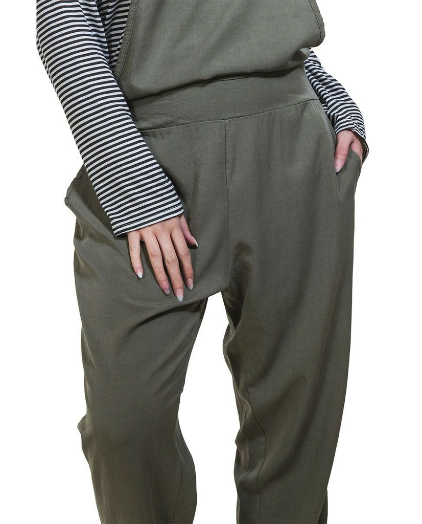 Focus on groin area with hand in left pocket of khaki catsuit and striped t-shirt.