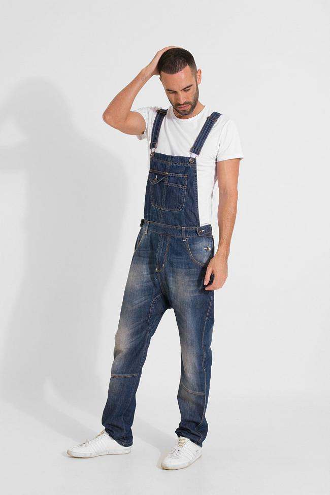 Angled full frontal pose with right hand on head. Model wearing dark wash organic dungarees from Dungarees Online.
