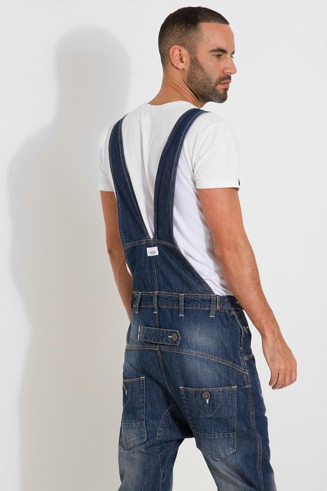 Rear side pose looking over right shoulder. Bottom of legs cropped with darkwash medium weight bib overalls.