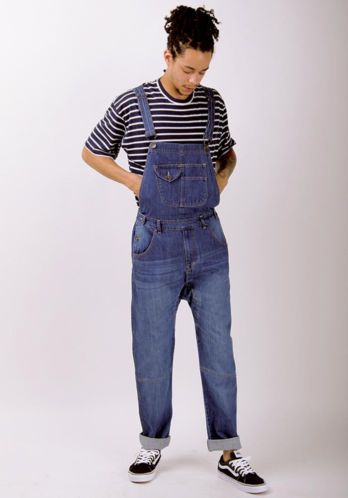 Looking down wearing mid-weight light wash dungarees with hands tucked behind bib.