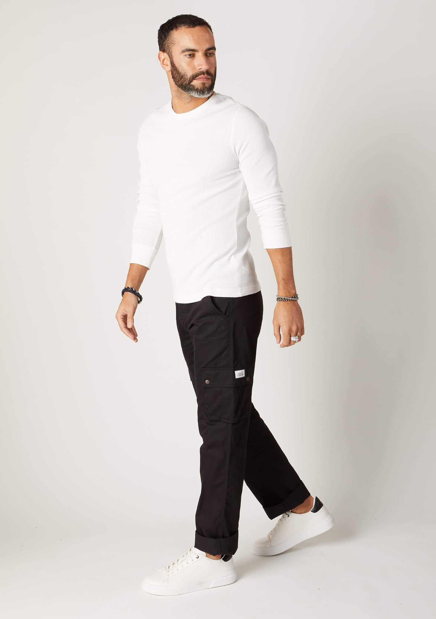 Walking pose, side-view of relaxed fit, organic cotton cargo trousers, with clear view of front cargo pockets.