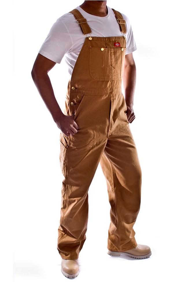 Angled frontal view of Dickies brown duck denim dungarees, detailing pockets, zip fly and triple stitched seams. Head cropped.