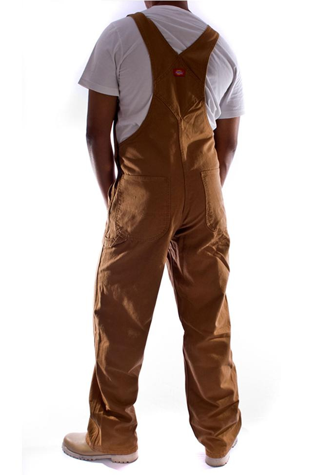 Back view of Dickies brown work duck denim dungarees, detailing triple stitched seams and cross over high back. Head cropped.