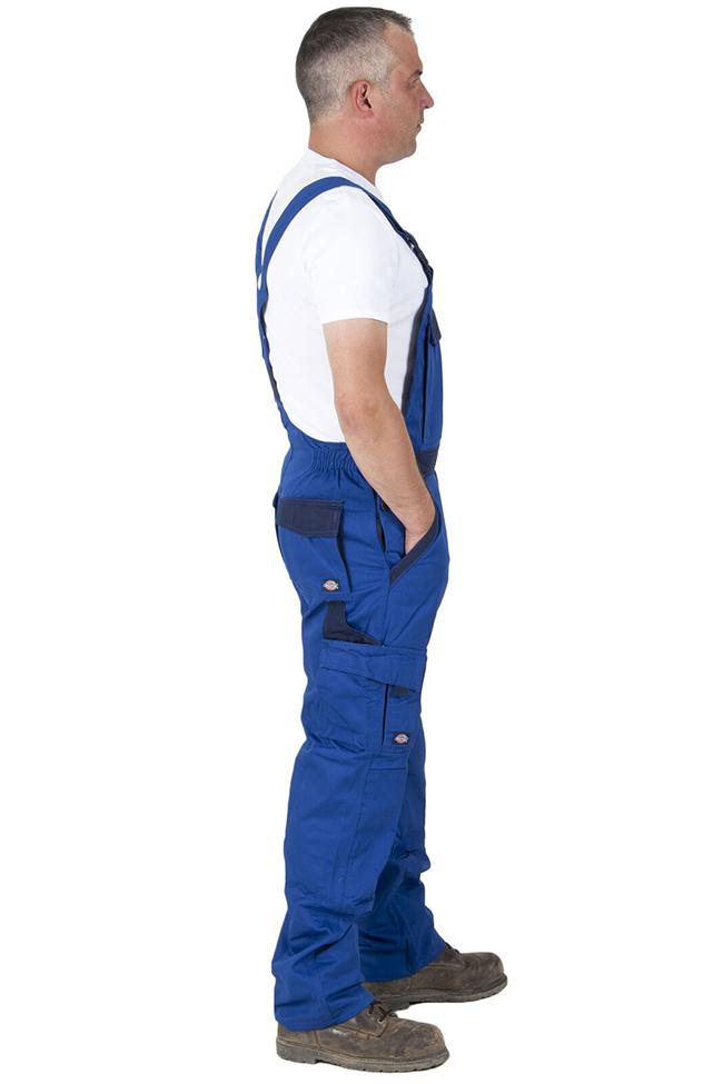 Full side view of Dickies blue work dungarees with hands in side pockets, detailing adjustable waist.