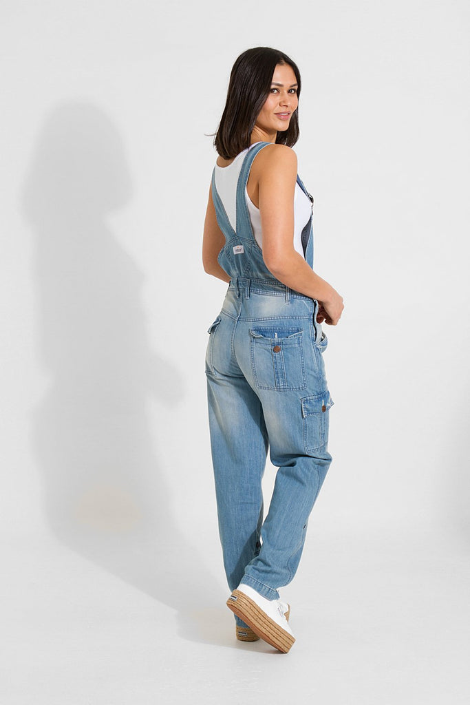 Full rear walking pose, while looking over her right shoulder, wearing light faded blue denim bib-overalls with abrasions.