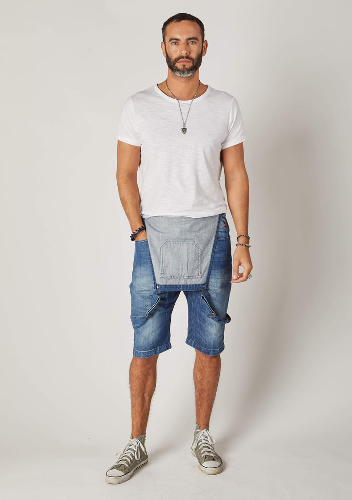 Full frontal shot of Dungarees Online's mid-blue, slim-fit, bib-overall shorts with bib down and right hand in pocket. Paired with white t-shirt and olive Converse.