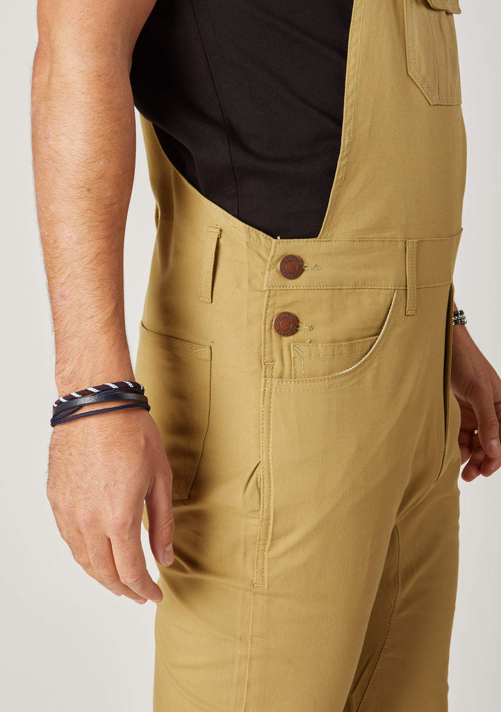 Close-up side view of men's slim-fit black khaki bib-overalls with clear view of side button fastening and belt loops.