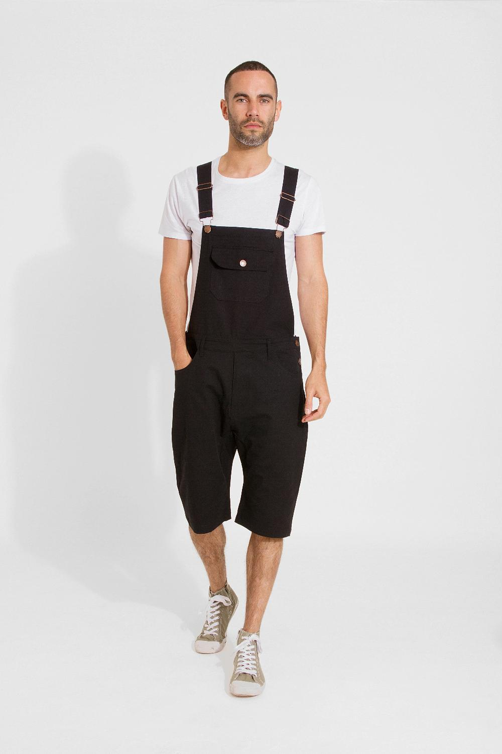 Full frontal walking pose wearing slim-fit, dark cotton bib-overall shorts from Dungarees Online.