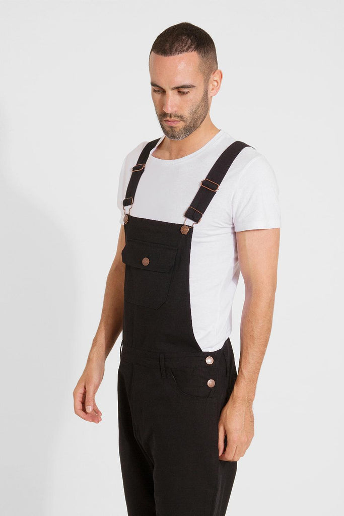 Top half focus of men's slim-fit black cotton bib-overalls with clear view of side button fastening, belt loops and adjustable straps.
