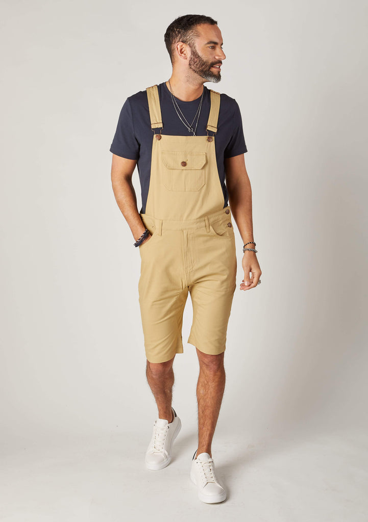 Full frontal walking pose wearing slim-fit, sand-coloured cotton bib-overall shorts from Dungarees Online. Hand in front-tight pocket with clear view of adjustable straps and large bib pocket.