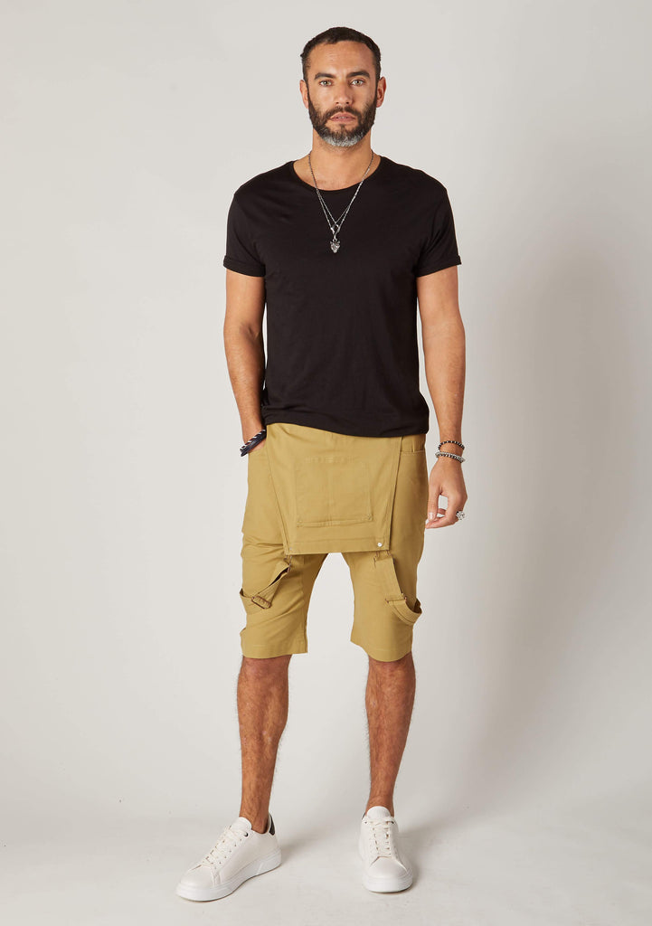 Full frontal bib-down view of slim-fit, khaki cotton bib-overall shorts from Dungarees Online, with hand in front-right pocket.