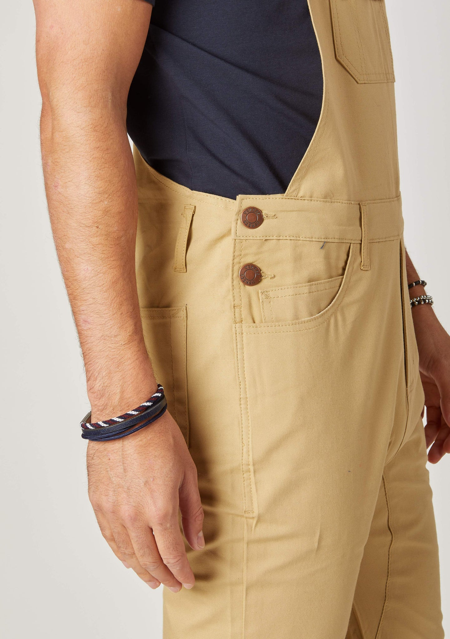 Close-up side view of men's slim-fit faded-yellow khaki bib-overalls with clear view of side button fastening and belt loops.