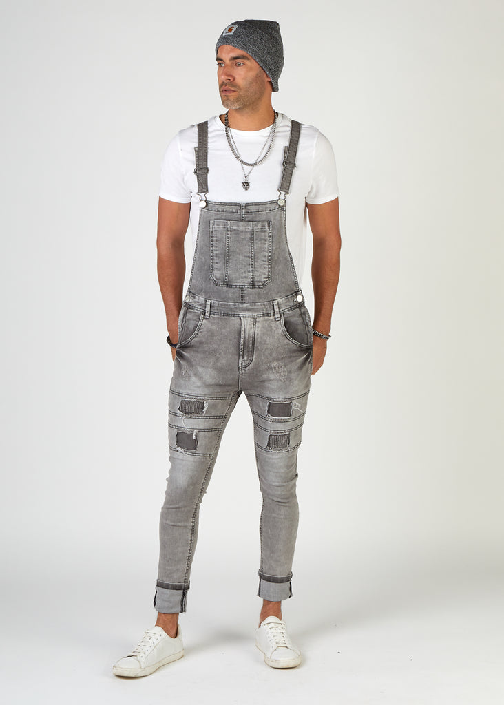 Model looking to his right wearing super slim fit men's grey distressed denim dungarees with legs turned up a bit