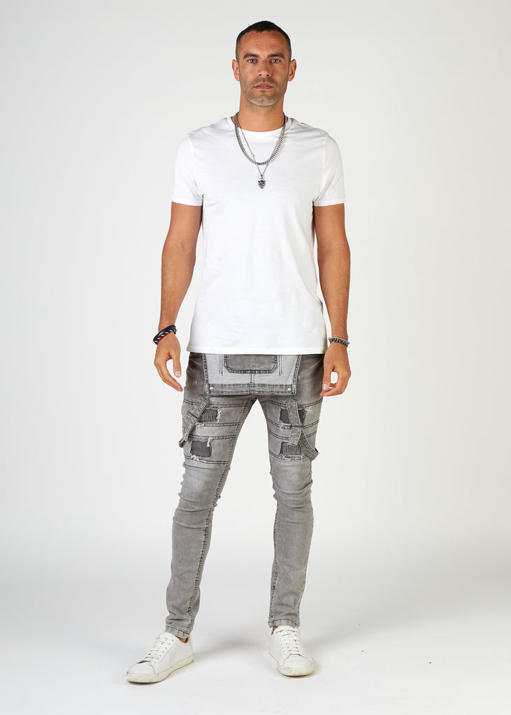 Front view, faded grey distressed denim overalls with bib down showing inside bib pocket