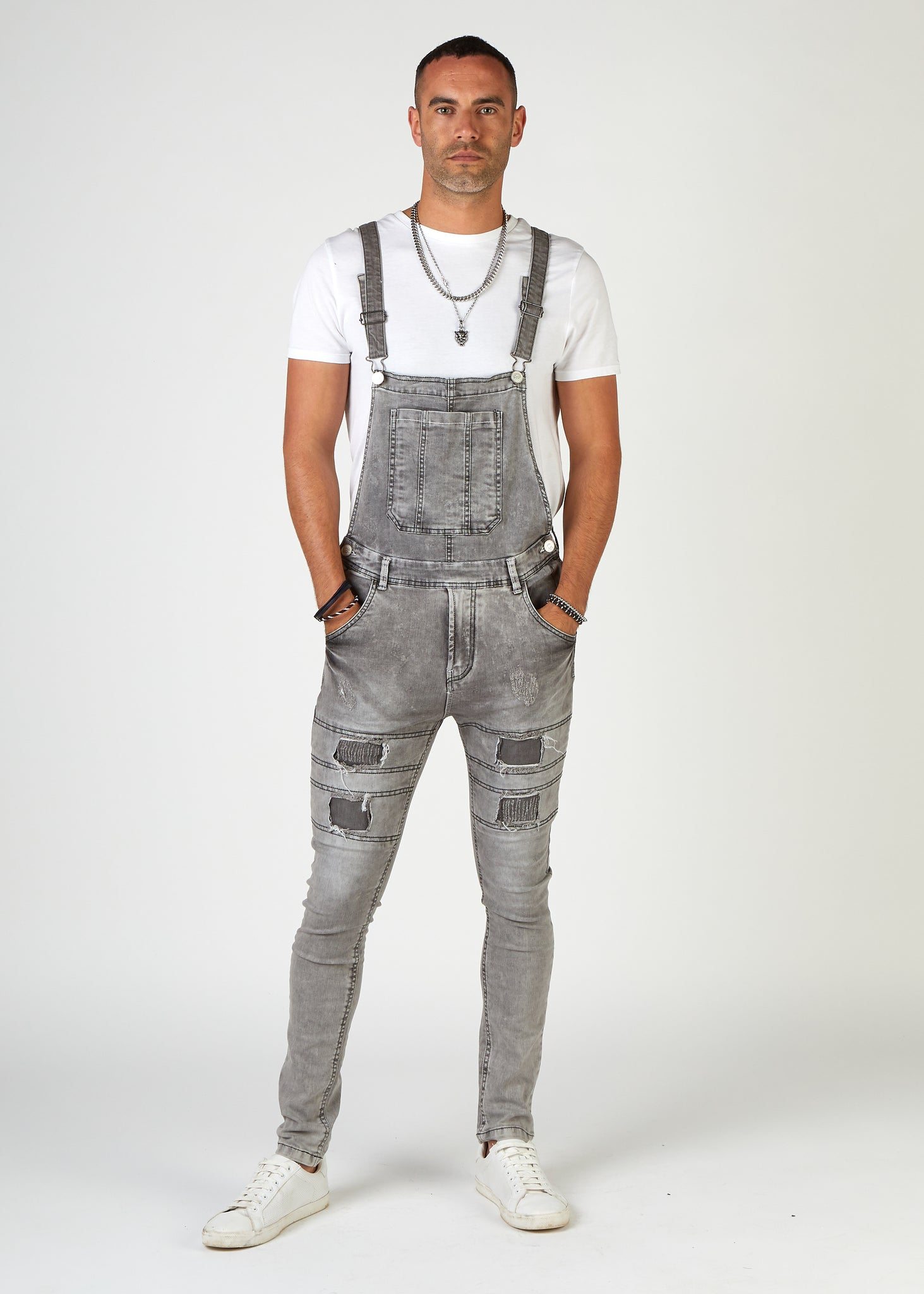 Frontal of 'Failsworth' brand men's super skinny bib overalls, with clear view of abrasions and repaired rips on thighs.