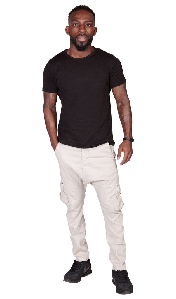 Full frontal view of 'Finley' style, casual, slight-stretch cotton cargo trousers in off-white with right hand in front pocket.
