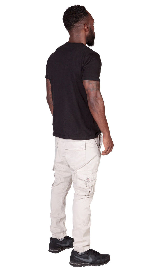 Full angled back-view wearing stone, cotton-mix combat trousers with clear view of cargo pockets.