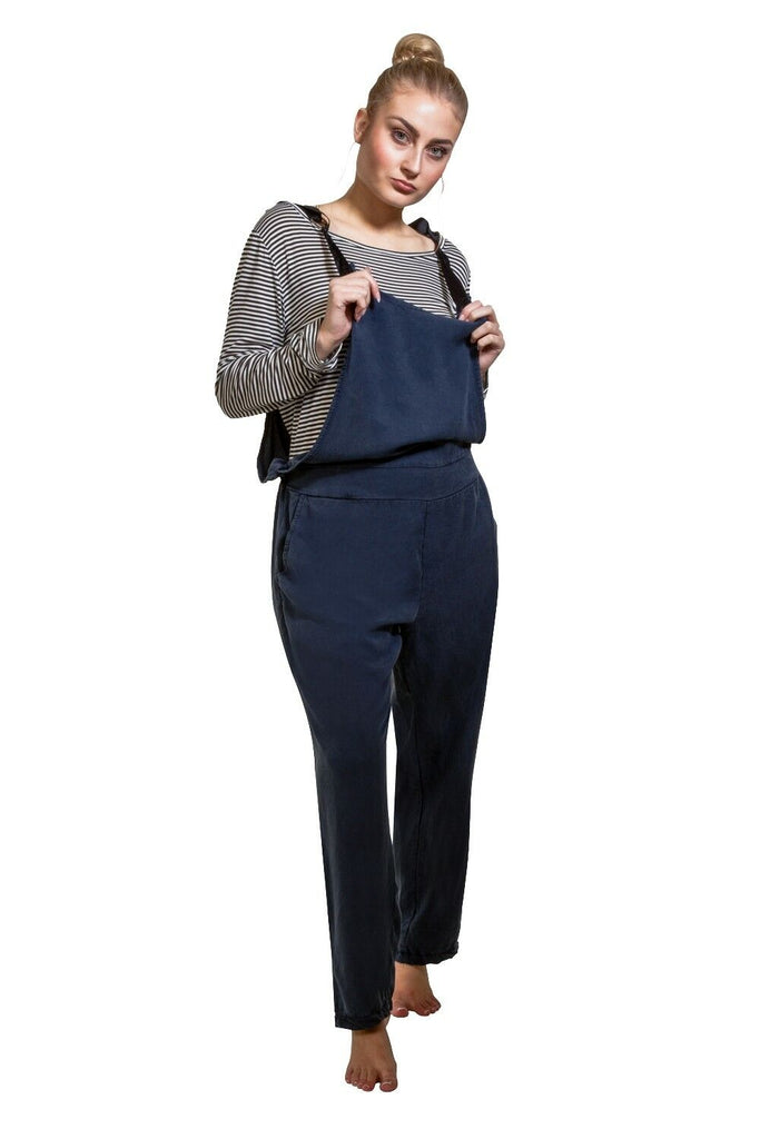 Full-length frontal pose, wearing lyocell navy blue jumpsuit and black and white hooped long-sleeved t-shirt, with nads on adjustable straps.