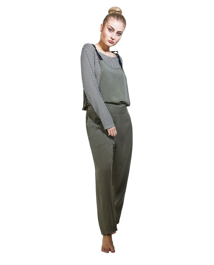 Full-length frontal pose, wearing khaki jumpsuit and black and white hooped long-sleeved t-shirt.