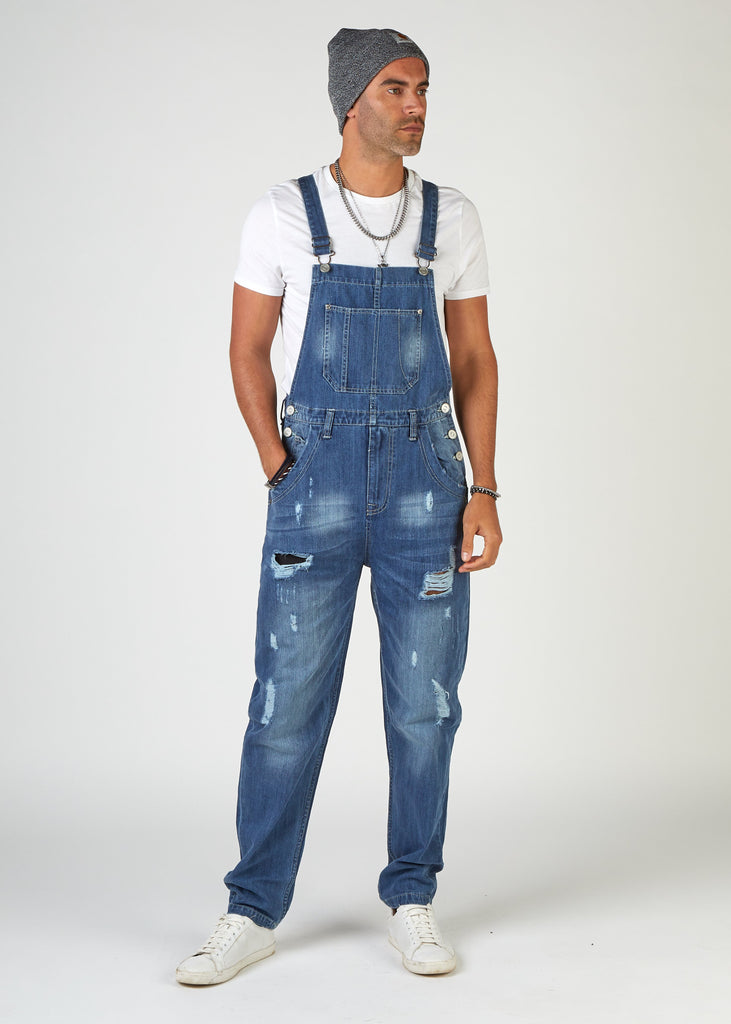Frontal, full-length pose, looking to model's left, wearing loose, midwash, ripped denim dungarees.