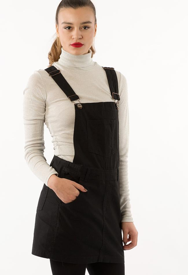 Top two-thirds frontal pose, wearing dark dungaree dress with right hand in front pocket.