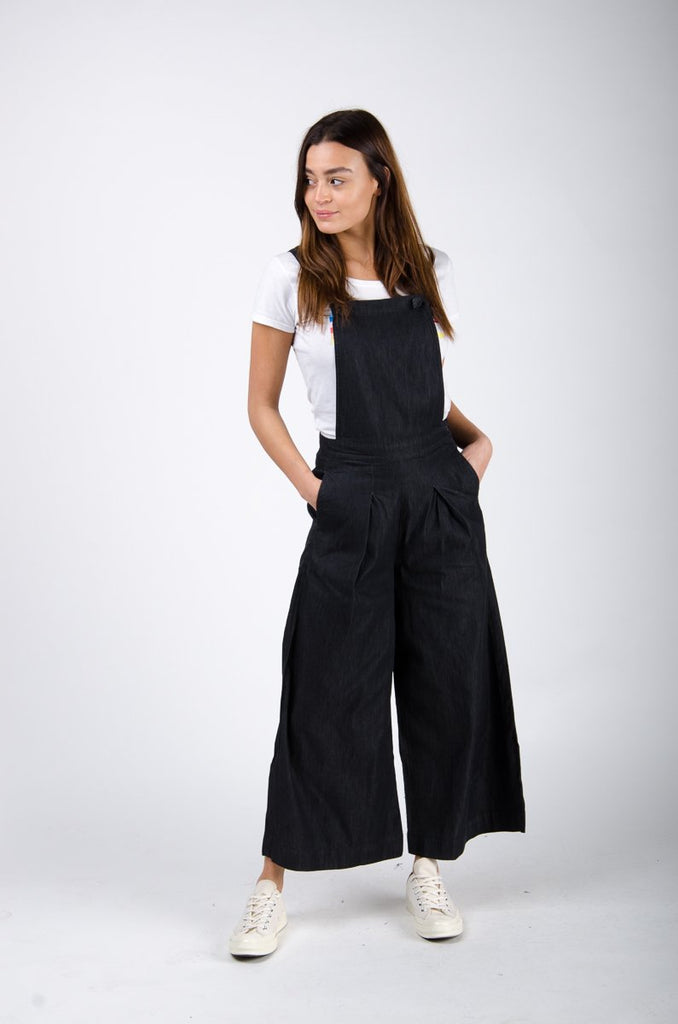 Front pose twisting right wearing black wide-leg bib overalls.