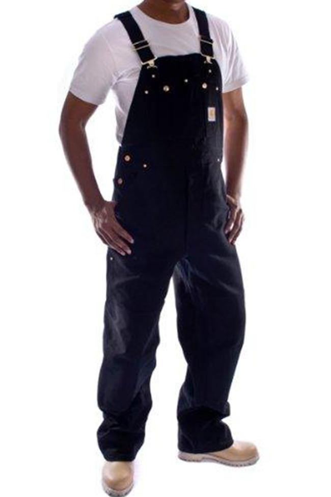 Angled frontal pose angled slightly left with thumbs in reinforced pockets, wearing Carhartt R01 black denim dungarees.