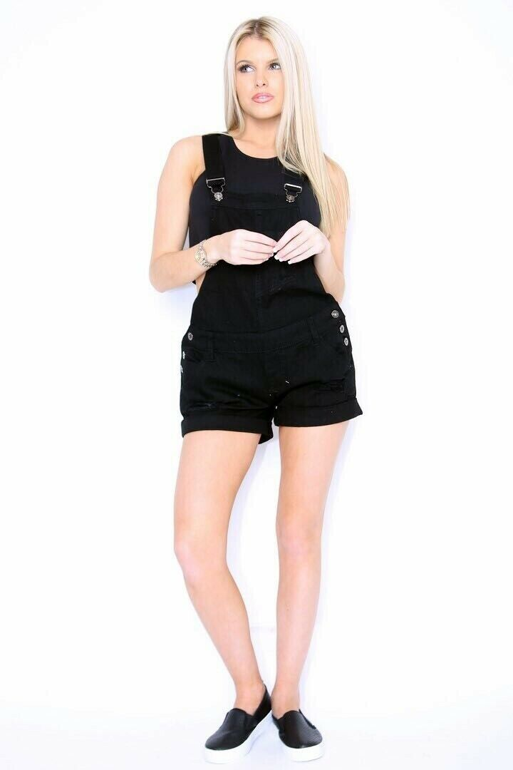 Full frontal pose with knees bent, wearing destroyed black denim overall shorts from Dungarees Online.