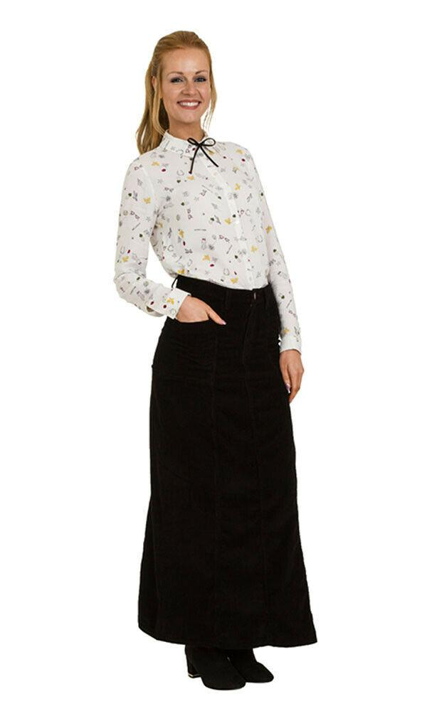 Front view of full-length black corduroy skirt with right hand in front pocket.