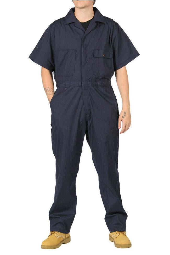 Full-length front view with hands in right pocket, wearing 'Key Apparel USA' relaxed-fit navy coverall, showing chest pockets.