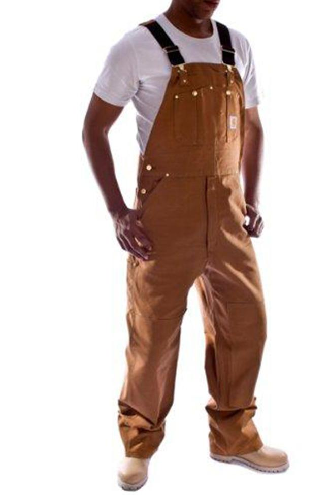 Angled frontal pose facing slightly left with thumbs in reinforced pockets, wearing Carhartt R01 brown denim dungarees.