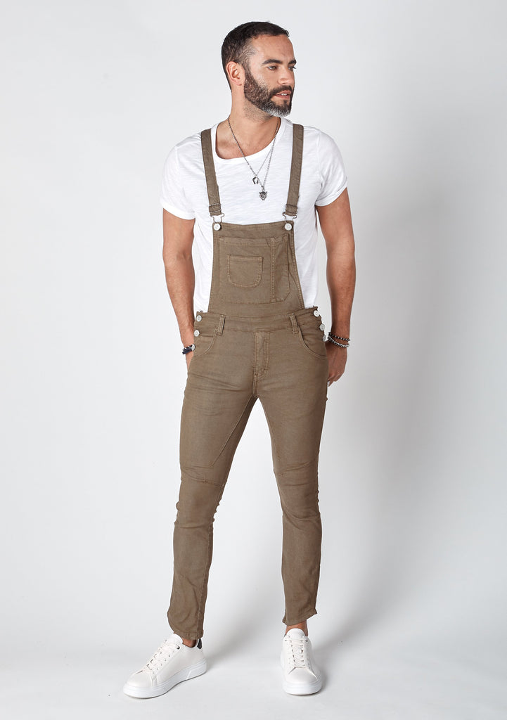 Frontal pose looking left with bib up wearing brown, 'Burton' brand skinny fit dungarees.
