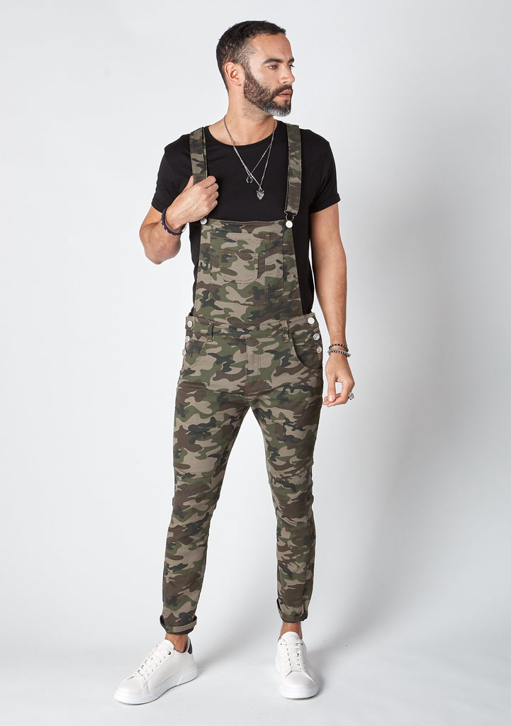 Frontal pose looking left with bib up wearing camouflage, 'Burton' brand skinny fit dungarees.