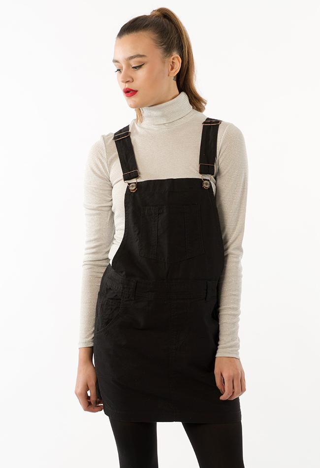 Frontal top two-thirds pose with model looking down and to right, with arms by her side, wearing oversized black denim dungaree dress.