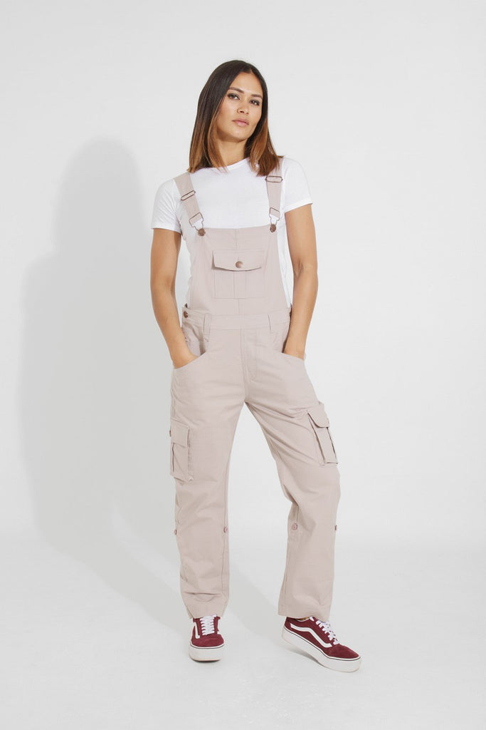 Full frontal with hands in both front pockets, wearing casual, loose fit beige dungaree from Dungarees Online.