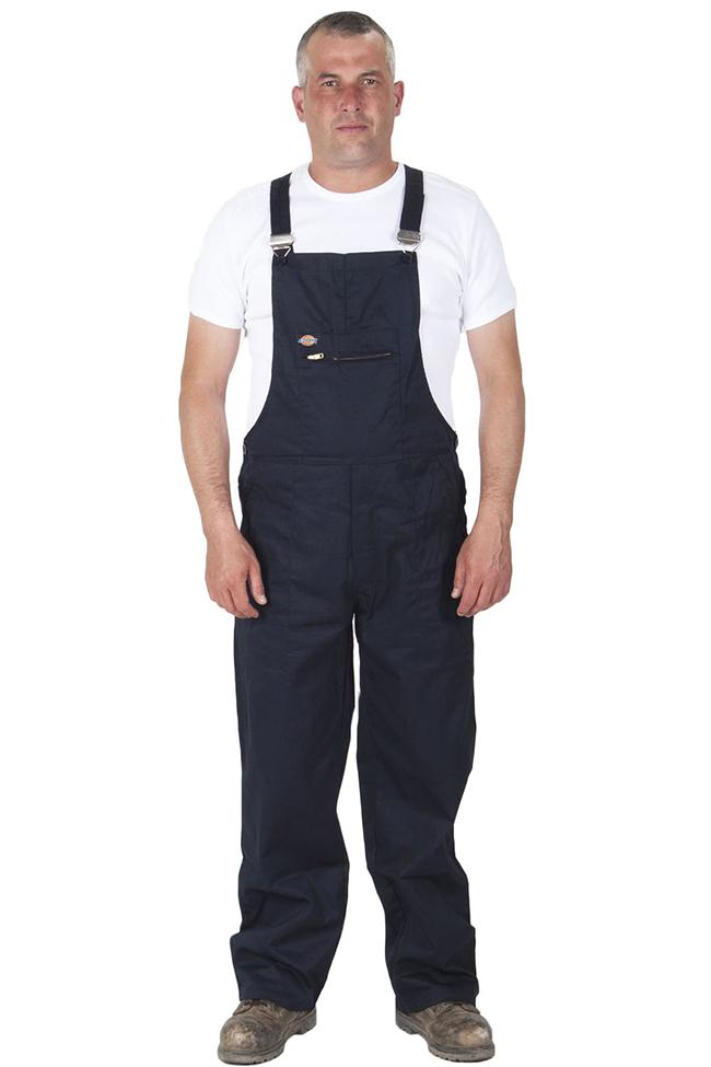 Full frontal pose wearing Redhawk black work dungarees showing bib pocket with zip.