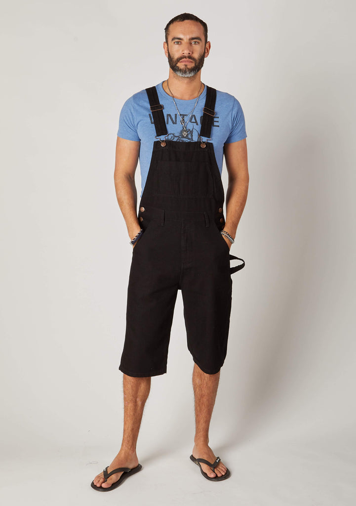 Full frontal pose wearing black denim bib overalls shorts.