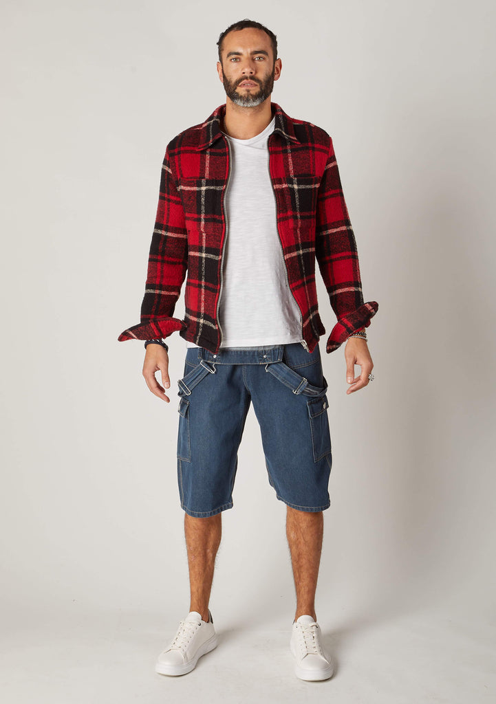 Full frontal pose wearing denim bib overalls shorts with bib down and shirt.