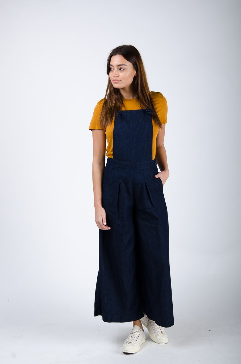 Front pose looking right wearing indigo wide-leg bib overalls.
