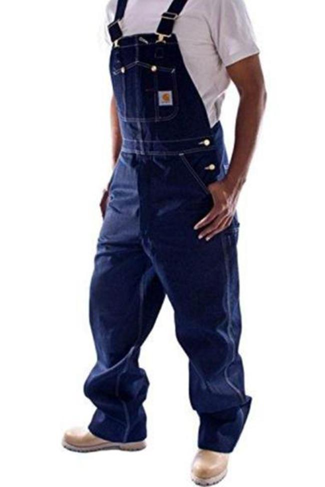 Angled frontal pose facing right with thumbs in reinforced pockets, wearing Carhartt R08 indigo denim dungarees.