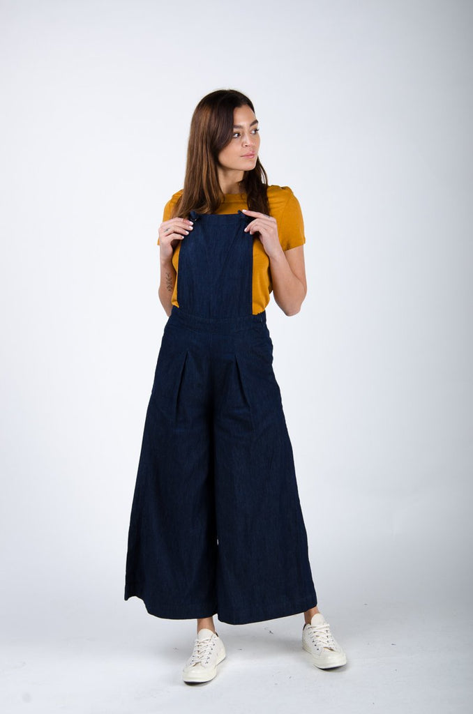 Front pose looking left, clutching straps on 'Bluebell' wide-leg bib overalls.