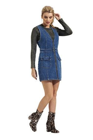 Full-length frontal of pinafore-style fitted sleeveless short denim dress in mid-wash denim.