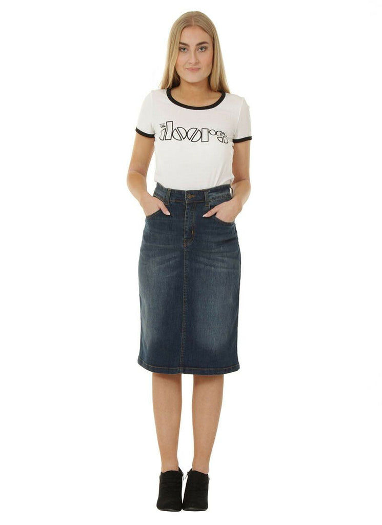 Full frontal view with hands in front pockets wearing classic below the knee, flexible denim skirt.