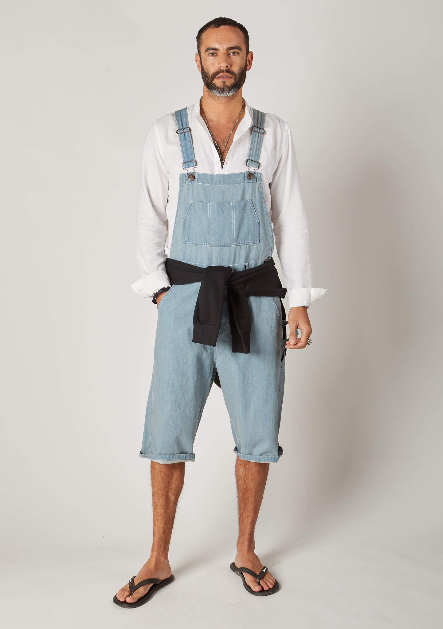 Full frontal pose looking forwards with hand in right pocket, wearing dungarees shorts for men with adjustable straps up.