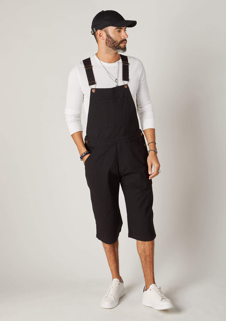 Full frontal pose angled to his right and walking, wearing bib-up black coloured dungaree shorts from Dungarees Online.